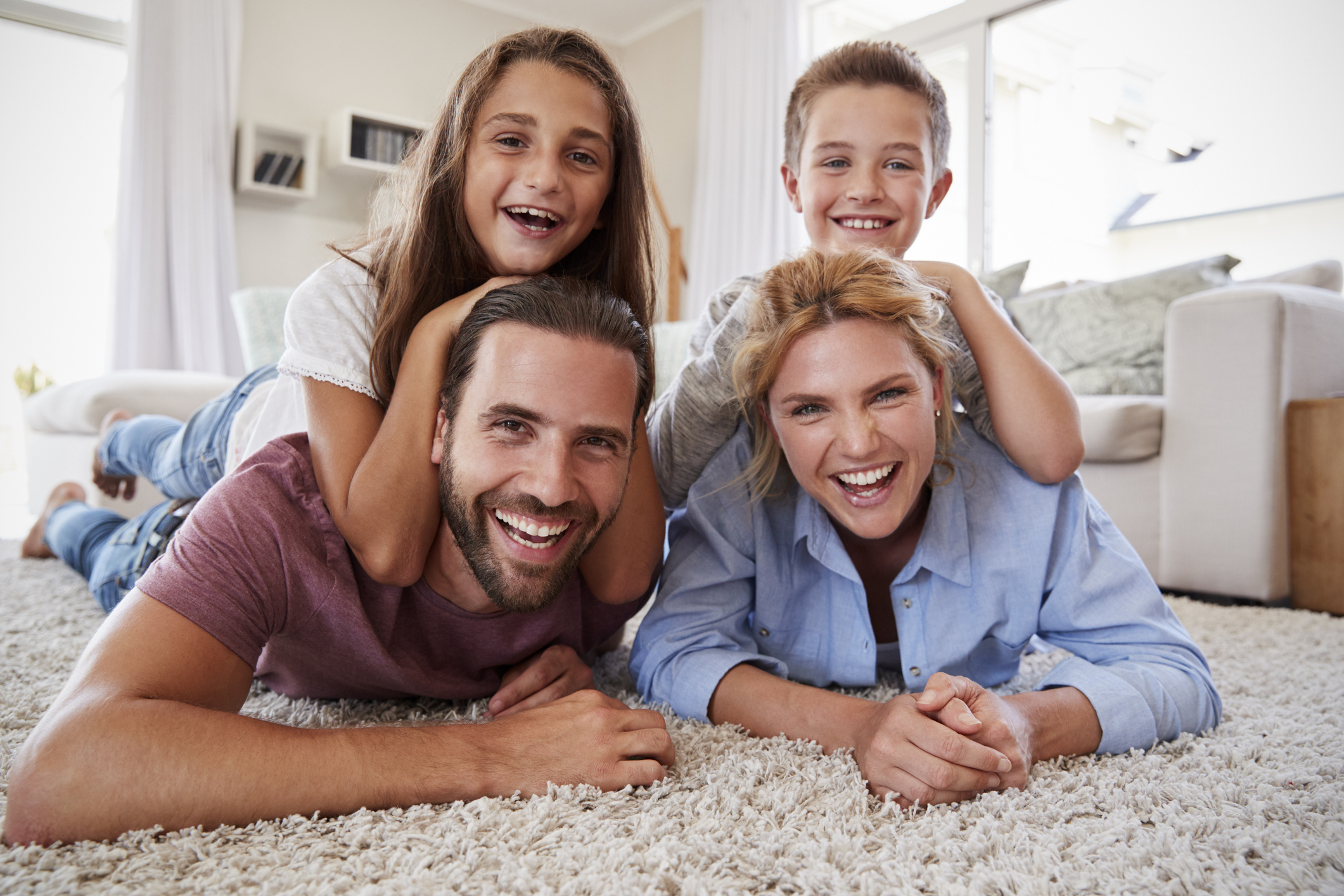 Portrait Of Family Lying On Rug In Lounge At Home